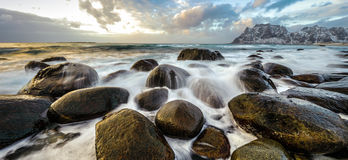 Movement of water on the shores of cold Norwegian Sea at evening time. Lofoten islands. Beautiful Norway landscape. Panoramic phot Royalty Free Stock Photos