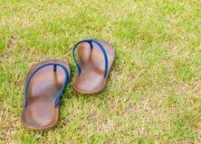 Movendo para a frente sandálias de borracha marrons velhas no campo de grama Fotografia de Stock Royalty Free