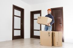 Mover with cardboard box at indoors of apartment. Relocation services man in hat holds boxes. Delivery man with parcel stock image