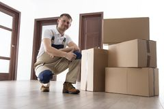 Mover with cardboard boxes in apartment. Relocation services. Loader holds thumb up royalty free stock photo