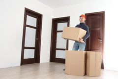 Mover with cardboard boxes in house stock image