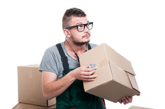 Mover guy checking cardboard box with stethoscope Stock Photo