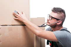 Mover guy checking cardboard box with stethoscope Royalty Free Stock Photography