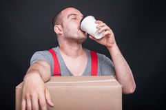 Mover guy drinking coffee from takeaway cup Stock Photo