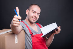 Mover guy holding agenda making thumb up gesture. On black background Royalty Free Stock Photos