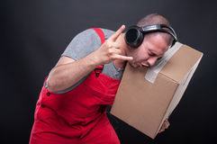 Mover guy holding box gesturing rock music Royalty Free Stock Image