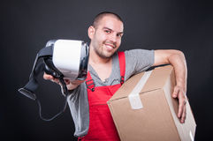 Mover guy holding box handing vr glasses. And smiling on black background Stock Photography