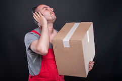 Mover guy holding box and listening to headset Stock Images