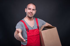 Mover guy holding box offering hand shake royalty free stock photo