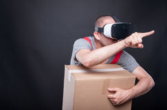 Mover guy holding box pushing button wearing vr glasses. On black background with copy text space Royalty Free Stock Images