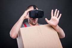 Mover guy holding box wearing vr glasses acting scared. On black background Stock Photos