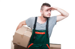 Mover guy holding cardboard box looking far away Stock Image