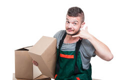 Mover guy holding cardboard box making call me gesture Stock Photos