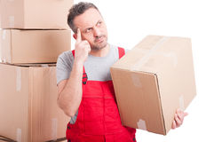 Mover guy holding cardboard box making thinking gesture Royalty Free Stock Photos