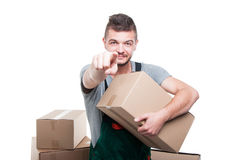 Mover guy holding cardboard box pointing camera. Handsome mover guy holding cardboard box pointing camera and smiling isolated on white background Royalty Free Stock Images