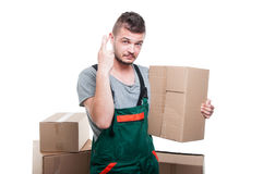 Mover guy holding cardboard box showing fingers crossed Royalty Free Stock Photo