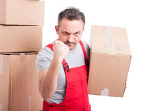 Mover guy holding cardboard box showing fist looking angry. Isolated on white background Royalty Free Stock Photography