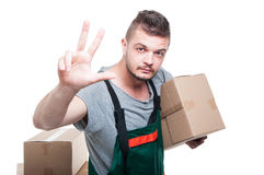 Mover guy holding cardboard box showing number three Stock Photos
