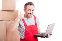 Mover guy holding laptop making calling gesture Royalty Free Stock Image