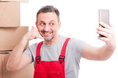 Mover guy making calling gesture taking selfie and smiling Royalty Free Stock Images