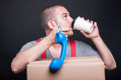 Mover guy sipping coffee playing with telephone receiver Stock Photos