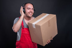 Mover guy smiling holding box and listening to headset Royalty Free Stock Image