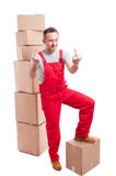 Mover guy standing on boxes showing obscene gesture. With both hands looking arrogant isolated on white background Stock Photography