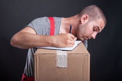 Mover guy taking notes from cardboard boxes. On black background Royalty Free Stock Images