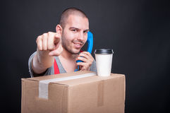 Mover guy talking on phone having coffee pointing camera. On cardboard box on black background Royalty Free Stock Photography