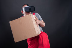 Mover guy wearing vr glasses acting scared. Holding cardboard box on black background Royalty Free Stock Photo