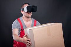 Mover guy wearing vr glasses handing cardboard box. On black background Royalty Free Stock Photos