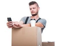 Mover man browsing and having coffee on boxes Royalty Free Stock Photography
