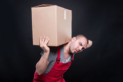 Mover man carrying heavy cardboard box. On black background Royalty Free Stock Image