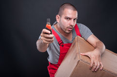 Mover man holding box and cutter tool looking serious. On black background with copypsace advertising area Stock Photos