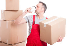 Mover man holding box and drinking coffee Royalty Free Stock Photography