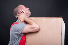 Mover man holding box having neck pain. Gesture on black background Royalty Free Stock Photography