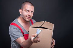 Mover man holding box showing some money. Mover man holding box and showing some money on black background Royalty Free Stock Image