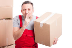 Mover man holding box and showing sush gesture Royalty Free Stock Photo