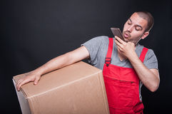 Mover man holding box taking photo with smartphone Stock Images