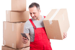 Mover man holding box and texting on smartphone. Isolated on white background Stock Images