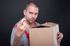 Mover man holding box wising bad luck with fingers crossed. On black background Stock Images