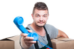 Mover man holding cardboard box handing telephone receiver. Mover man holding cardboard box handing big blue telephone receiver isolated on white background Royalty Free Stock Image