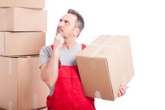 Mover man holding cardboard box making thinking gesture Royalty Free Stock Photos