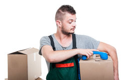 Mover man holding cardboard box putting dow telephone receiver. Isolated on white background Royalty Free Stock Photo