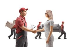Mover shaking hands with a woman and movers carrying furniture i royalty free stock image