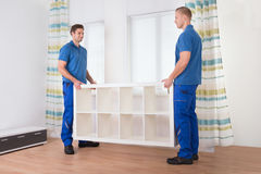 Movers Carrying Shelf At Home Royalty Free Stock Photos