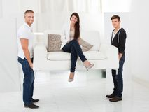 Movers carrying sofa with client. Full length portrait of movers carrying sofa with happy client women sitting Royalty Free Stock Photos