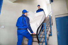 Movers Carrying Sofa On Steps. Male movers carrying sofa while climbing steps at home royalty free stock photo