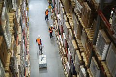 Movers and Loaders Working in Warehouse. Above view of warehouse workers moving goods and counting stock in aisle between rows of tall shelves full of packed Royalty Free Stock Images