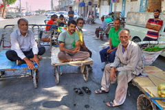 Movers with Oriental bazaar rest sitting on hand carts Royalty Free Stock Photos